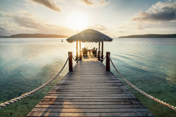 Vanuatu Romantic Sunset Jetty Efate Island Romantic vacations scene. Wooden jetty with table and lounge chairs towards the beautiful lagoon during sunset over Moso Island. Havannah, Efate Island, Vanuatu vanuatu stock pictures, royalty-free photos & images