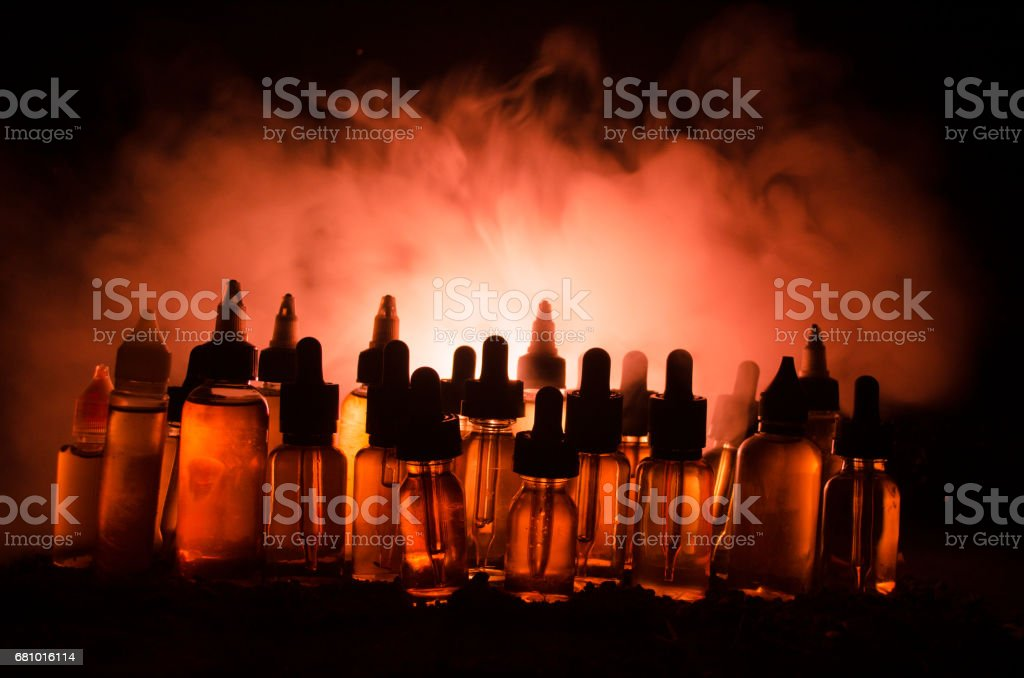 Vape concept. Smoke clouds and vape liquid bottles on dark background. Light effects. stock photo