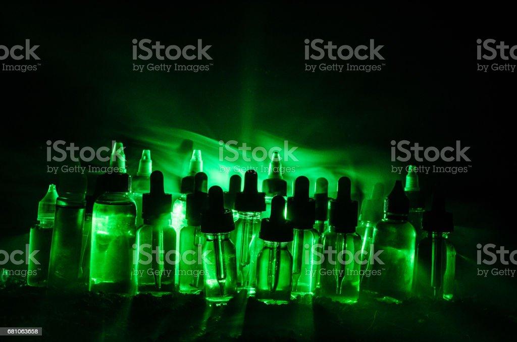 Vape concept. Smoke clouds and vape liquid bottles on dark background. Light effects. royalty-free stock photo