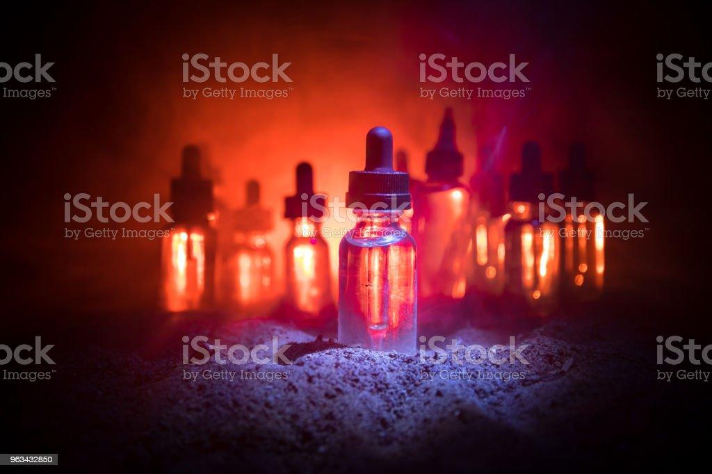 Vape concept. Smoke clouds and vape liquid bottles on dark background. Light effects. Useful as background or vape advertisement or vape background. - Zbiór zdjęć royalty-free (Atomizer do perfum)