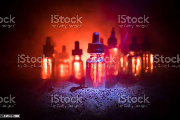 Koncepcja Vape Chmury Dymu I Butelki Płynu Vape Na Ciemnym Tle Efekty Świetlne Przydatne Jako Tło Lub Vape Reklamy Lub Vape Tle - zdjęcia stockowe i więcej obrazów Atomizer do perfum
