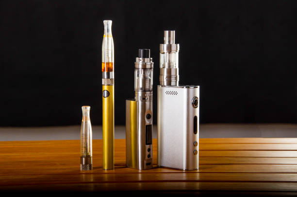 vape devices and electronic cigarette, ecig and mods over a black background. Popular vaping e cig devices mod.electronic cigarette over a wood background. vaporizer e-cig old device model. nicotine stock pictures, royalty-free photos & images