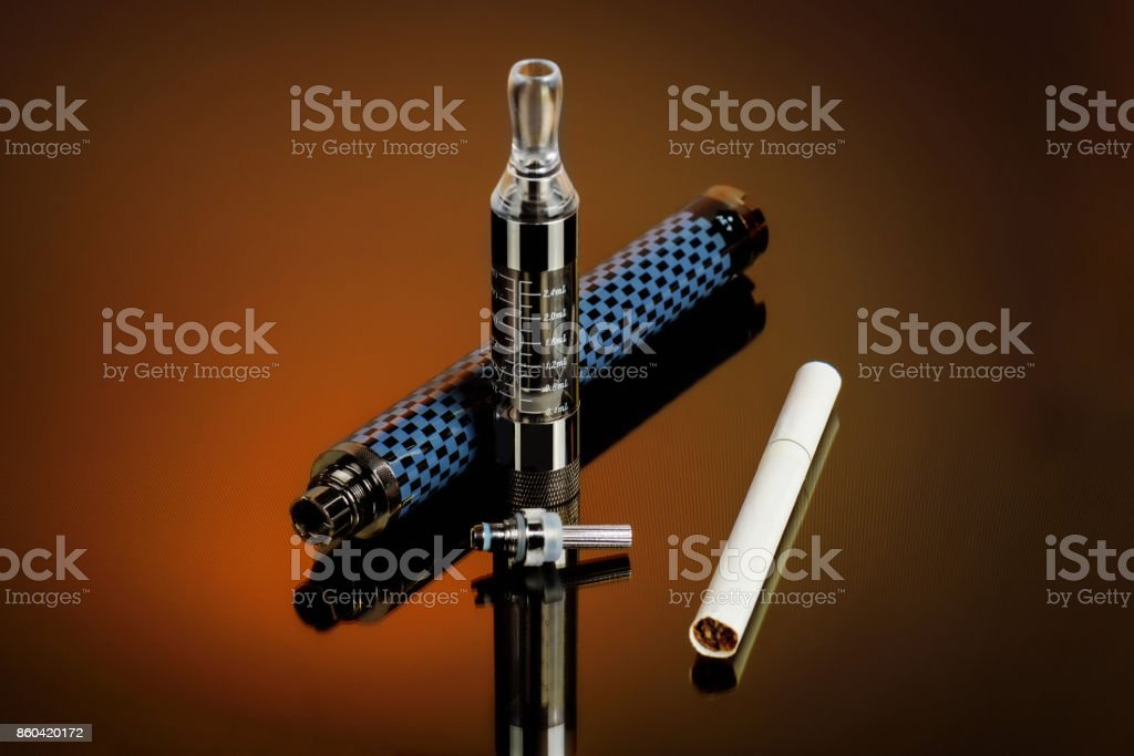 Vape, electronic cigarette exploded next to a conventional cigarette. stock photo