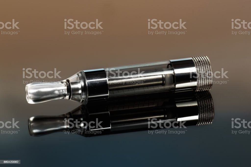 Vape, electronic cigarette exploded next to a conventional cigarette on a dark background with a gradient. stock photo