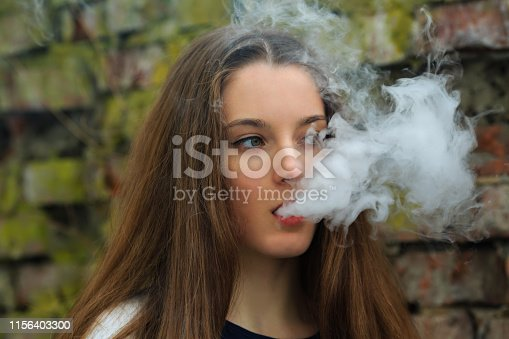 Vape teenager. Young pretty white girl in white cardigan smoking an electronic cigarette opposite destroyed brick wall on the street in the spring. Bad habit that is harmful to health.