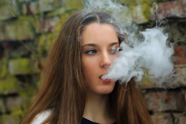 vape 십대. 흰색 가디건에서 젊은 예쁜 흰색 소녀는 봄에 거리에서 파괴 벽돌 벽 맞은 편 전자 담배를 흡연. 나쁜 습관. - 전자담배 뉴스 사진 이미지