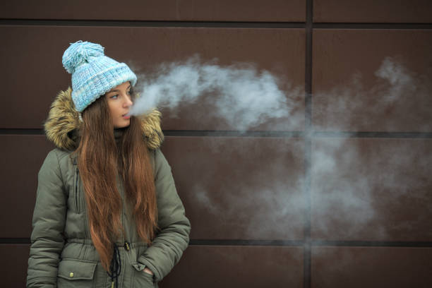 Vape teenager. Young pretty white girl smoking an electronic cigarette opposite modern brown background on the street in the winter. Vape teenager. Young pretty white girl in a cap smoking an electronic cigarette opposite modern brown background on the street in the winter. Bad habit. Close up. electronic cigarette stock pictures, royalty-free photos & images