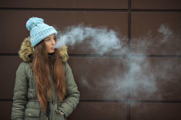 vape 십 대. 젊은 예쁜 백인 소녀 겨울에 거리에 현대 갈색 배경 맞은편 전자 담배를 흡연. - 전자담배 뉴스 사진 이미지