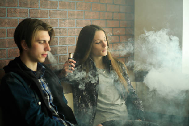 Vape teenagers. Young cute girl in sunglasses and young handsome guy smoke an electronic cigarettes in the vape bar. Bad habit that is harmful to health. Vape teenagers. Young cute girl in sunglasses and young handsome guy smoke an electronic cigarettes in the vape bar. Bad habit that is harmful to health. Vaping activity. electronic cigarette stock pictures, royalty-free photos & images