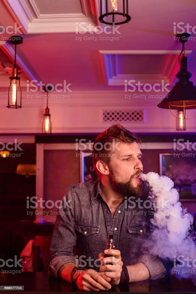 Vape. Vaping man in a cloud of vapor. Photo is taken in a vape bar stock photo