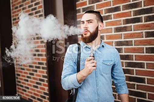 689660424 istock photo Vaping. Casual men with beard vaping an electronic cigarette. 626682808