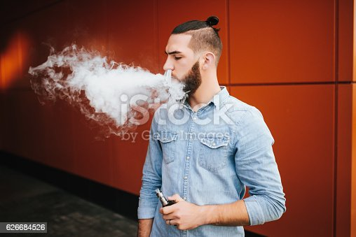 689660424 istock photo Vaping. Casual men with beard vaping an electronic cigarette. 626684526