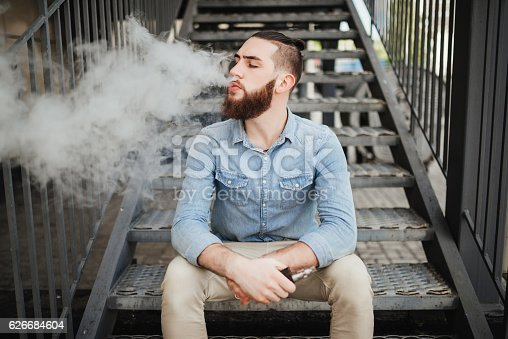 689660424 istock photo Vaping. Casual men with beard vaping an electronic cigarette. 626684604