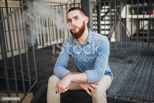 689660424 istock photo Vaping. Casual men with beard vaping an electronic cigarette. 626684946