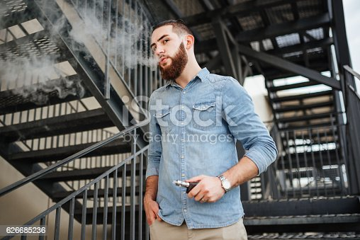689660424 istock photo Vaping. Casual men with beard vaping an electronic cigarette. 626685236