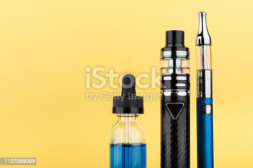 1137088939 istock photo vaping devices and bottle with vape liquid on yellow background 1137089069