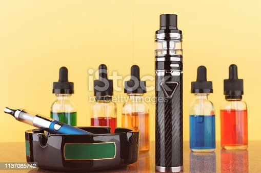 1137088939 istock photo vaping devices and bottles with vape liquid on yellow background 1137085742