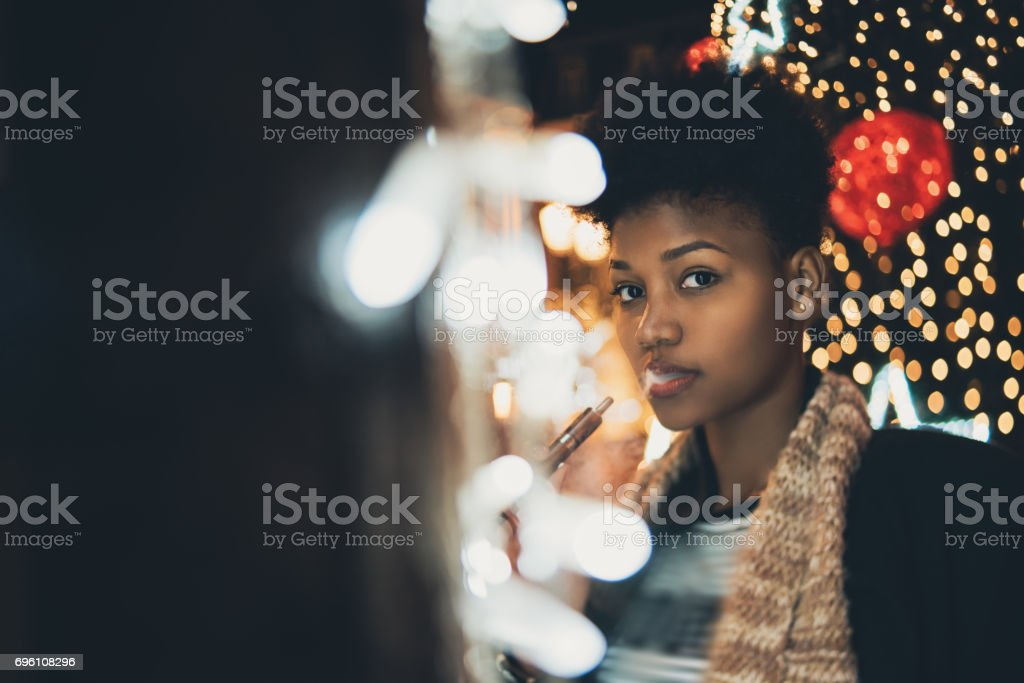 Vaping girl on night city street stock photo