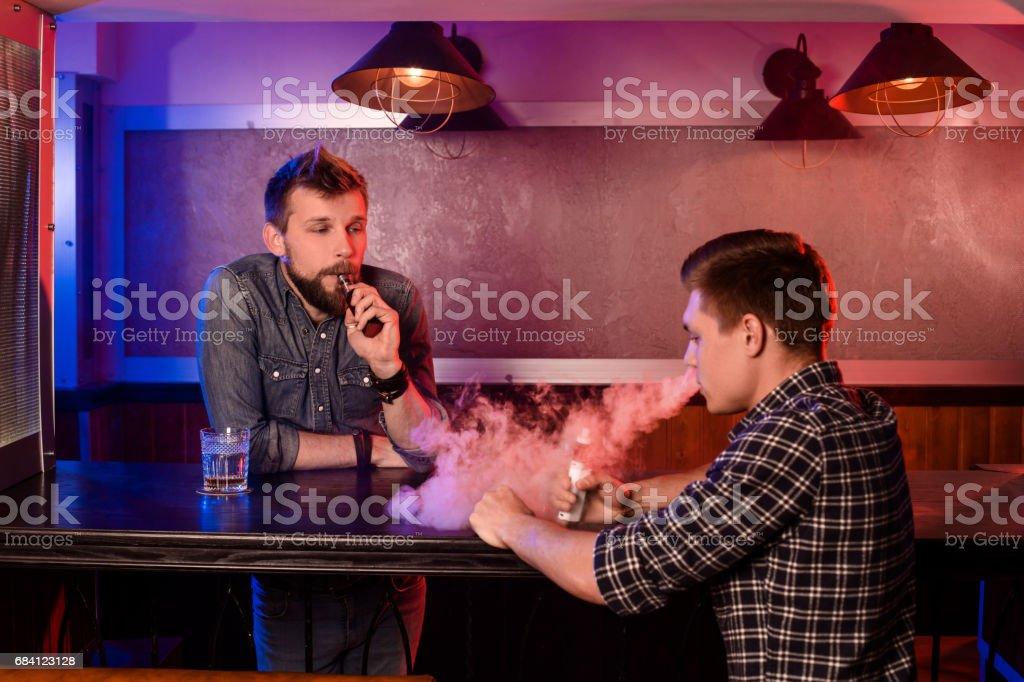 Vaping man holding a mod. A cloud of vapor at the vapebar stock photo