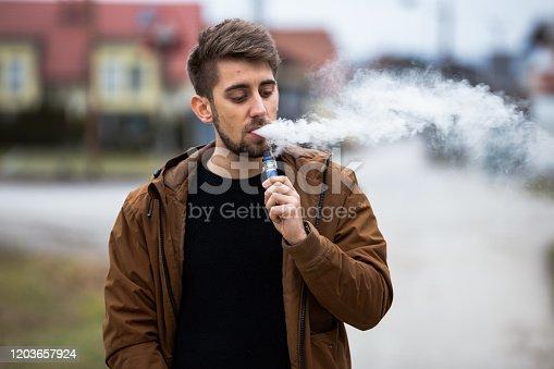 Man smoking with a blue vape.