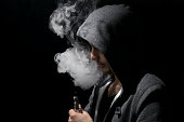 Man with hoody vaping an ecig, electronic cigarette.