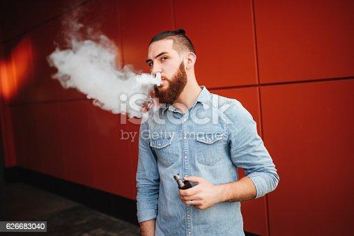 689660424 istock photo Vaping. Men with beard vaping electronic cigarette outdoor. 626683040