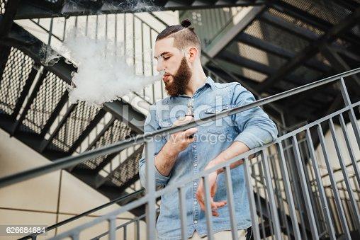 689660424 istock photo Vaping. Men with beard vaping electronic cigarette outdoor. 626684684