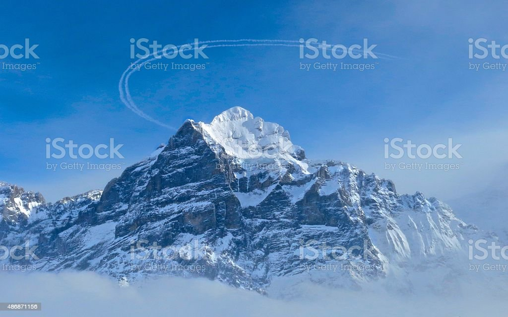 Vapor trail above snow-capped mountain winter in the Swiss Alps stock photo