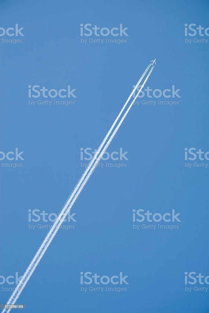 Vapor trail behind flying airplane royalty-free stock photo