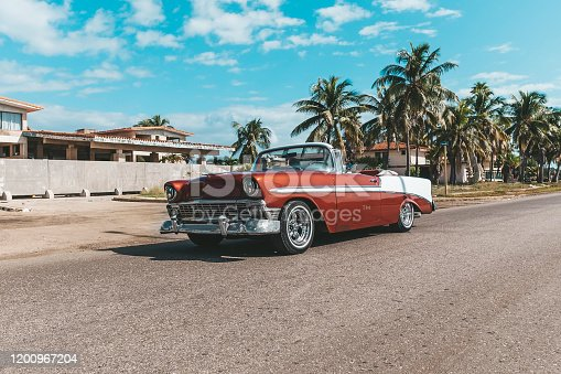 Varadero, Cuba. November 22, 2019: american Chevrolet Oldtimer rides on the road against the background of palm trees on the island of Cuba.