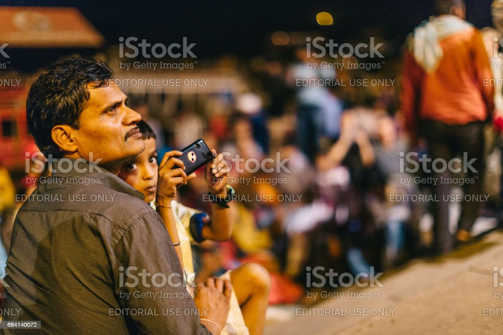 Varanasi, India: Father and his son, who his holding a mobile phone, are attending the Ganga Aarti, which is a religious ritual honoring Lord Shiva that takes place by the Ganges every evening at the holy Dashaswamedh ghat. foto stock royalty-free