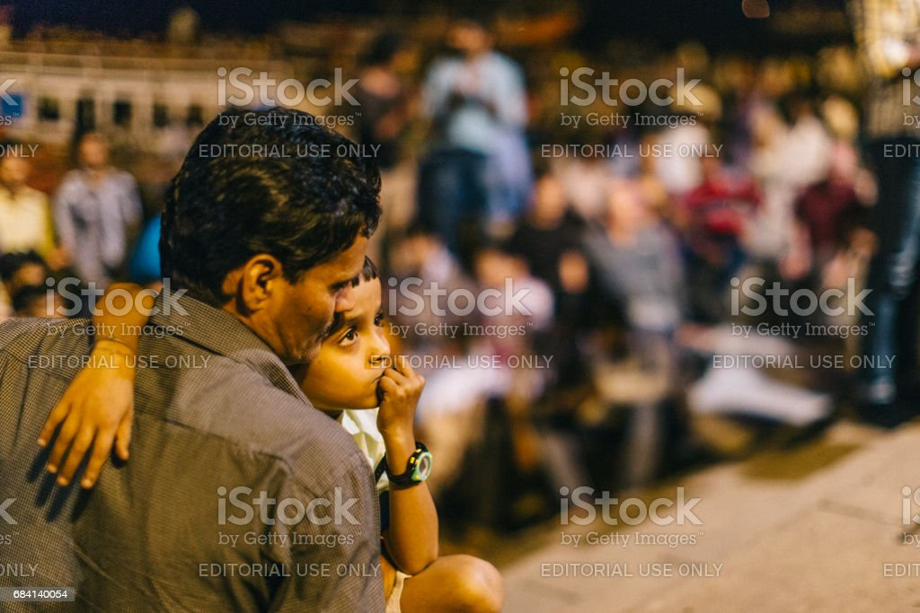 Varanasi, India: Father and son are attending the Varanasi Ganga Aarti, which is a religious ritual honoring Lord Shiva that takes place by the Ganges every evening at the holy Dashaswamedh ghat. zbiór zdjęć royalty-free
