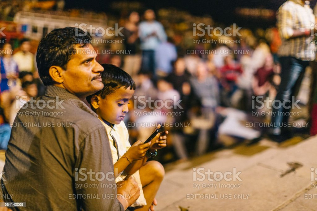 Varanasi, India: Father and son, who his holding a mobile phone, are attending the Ganga Aarti, which is a religious ritual honoring Lord Shiva that takes place by the Ganges every evening at the holy Dashaswamedh ghat. zbiór zdjęć royalty-free