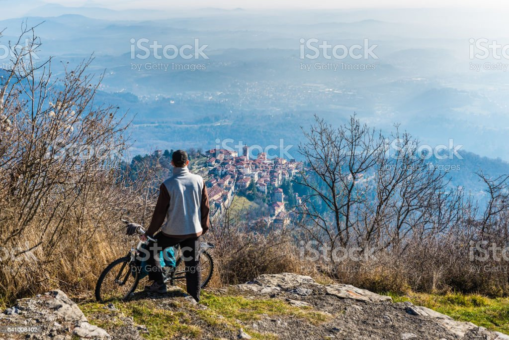 Varese, Italy: panorama of the small village Sacro Monte and cyclist with mtb stock photo