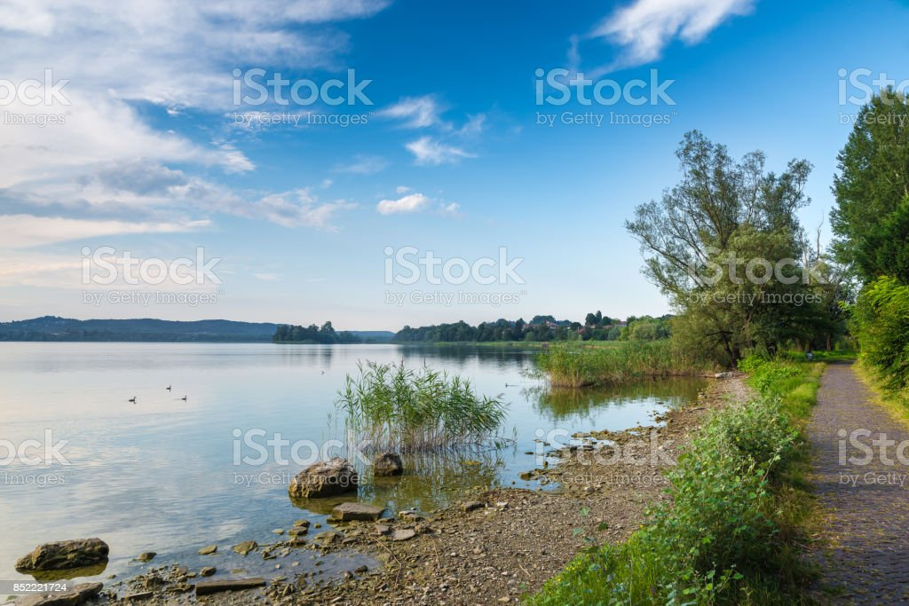 Varese Lake with Virginia islet (isolino Virginia)) and a stretch of the pedestrian cycle track around the lake, Biandronno, Italy. The island is a site of prehistoric finds, from 2011 added to the UNESCO World Heritage Site stock photo