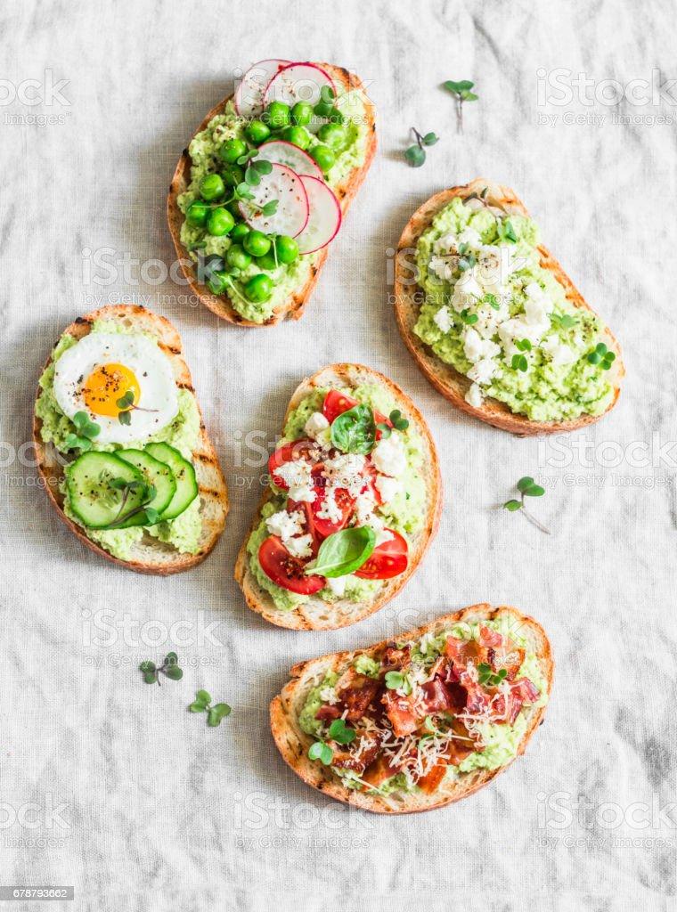 Varyasyon avokado sandviç - gevrek domuz pastırması, Bıldırcın yumurta, domates, keçi peyniri, yeşil bezelye, turp, salatalık ile. Sağlıklı snack. Hafif bir arka plan üzerinde görünümü top royalty-free stock photo