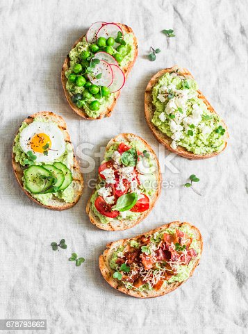 istock Variation avocado sandwich - with crispy bacon, quail egg, tomatoes, goat cheese, green peas, radish, cucumber. Healthy snack. On a light background, top view 678793662