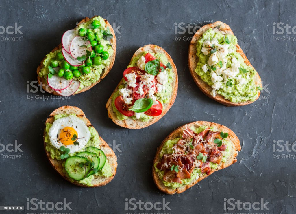 Variation avocado sandwich - with crispy bacon, quail egg, tomatoes, goat cheese, green peas, radish, cucumber. Healthy snack. On a dark background, top view royalty-free stock photo