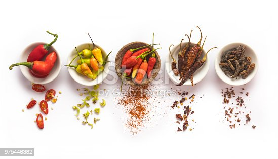 Properly isolated on a pure white background, a series of several cups with a variation of different chili pepper spices. Studio shot and directly above.