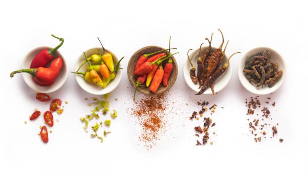 variatie van chili kruiden in kom geïsoleerd op witte achtergrond - peper specerij stockfoto's en -beelden