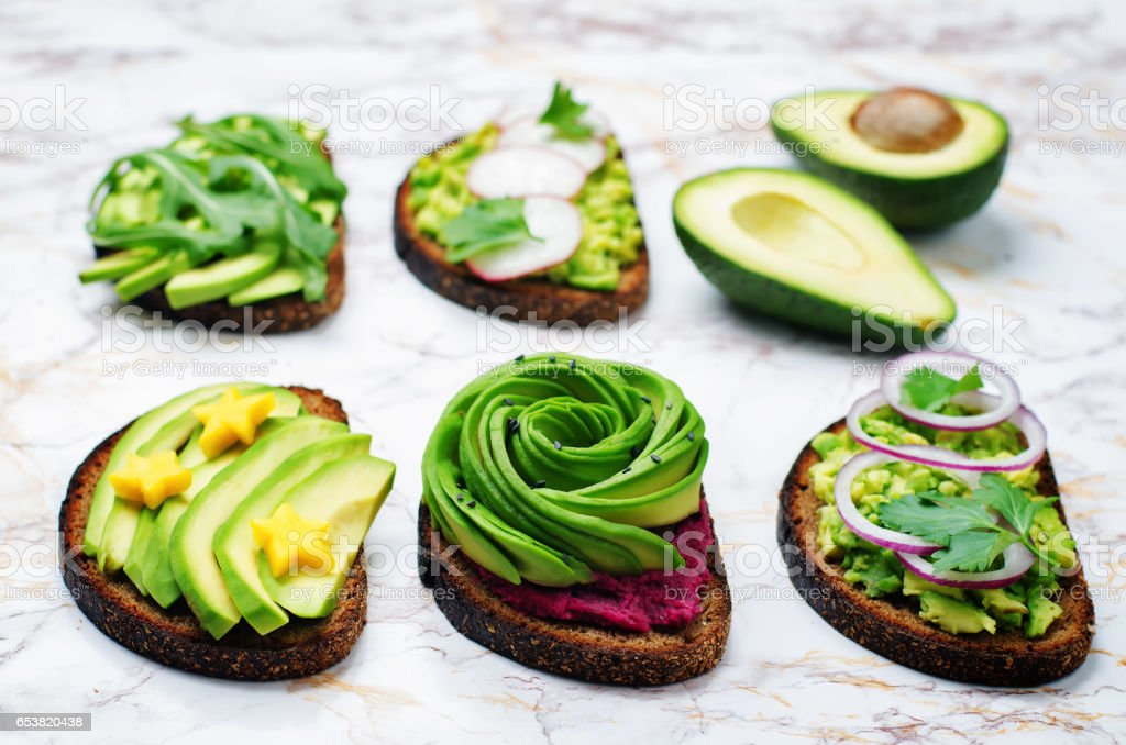 Variation of healthy rye breakfast sandwiches with avocado and toppings stock photo
