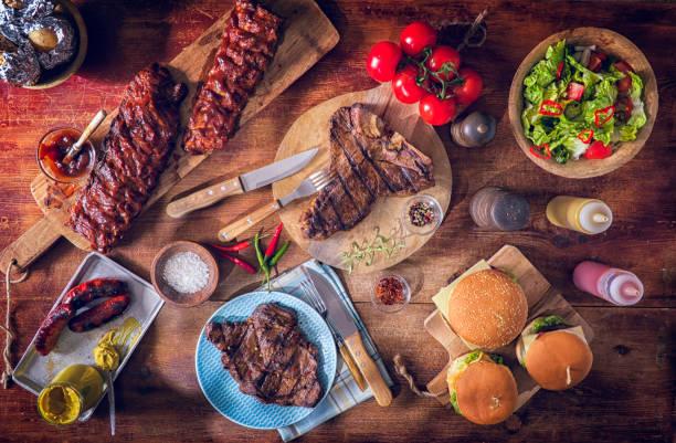 Variación de asados BBQ Rib Eye, t-Bone Steak, costillas y hamburguesas - foto de stock