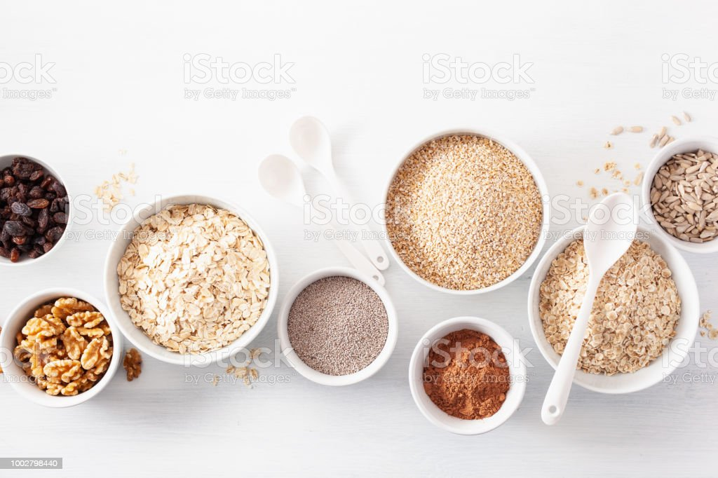 variaty of raw cereals and nuts for breakfast. Oatmeal flakes and steel cut, barley, walnut, chia, raisins. Healthy ingredients stock photo