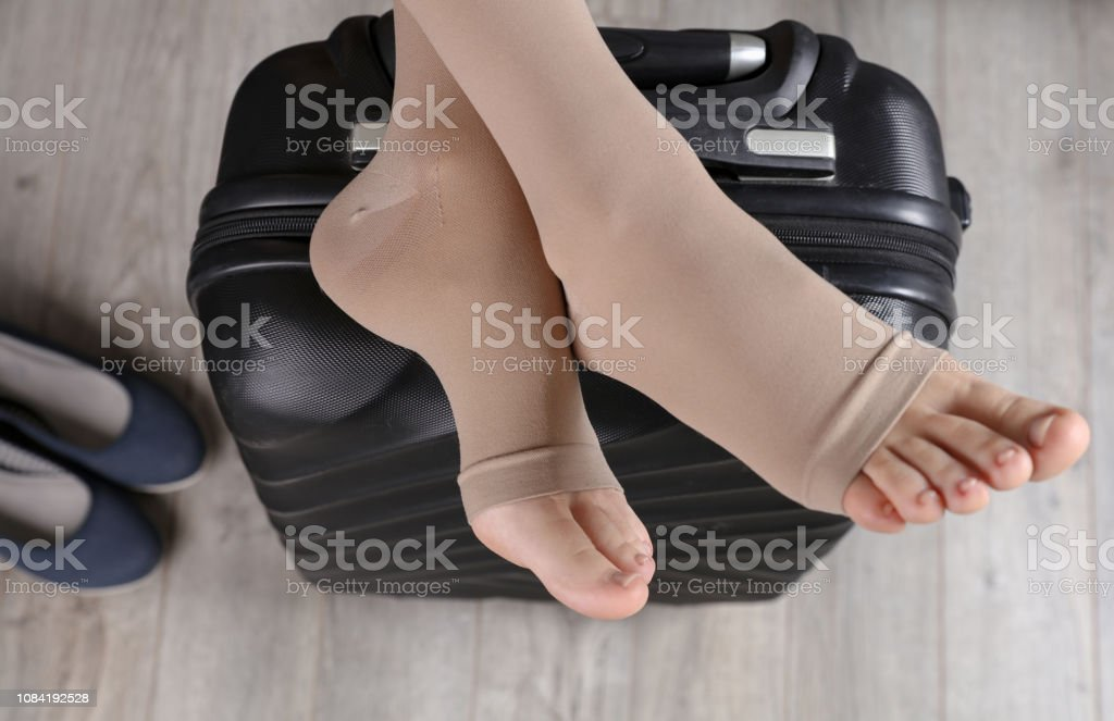 Varicose veins prevention, wearing Compression Stockings Thigh during flight stock photo