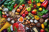 Food and drink large arrangement with carbohydrates protein vegetables and fruits legumes and dairy products on rustic board table