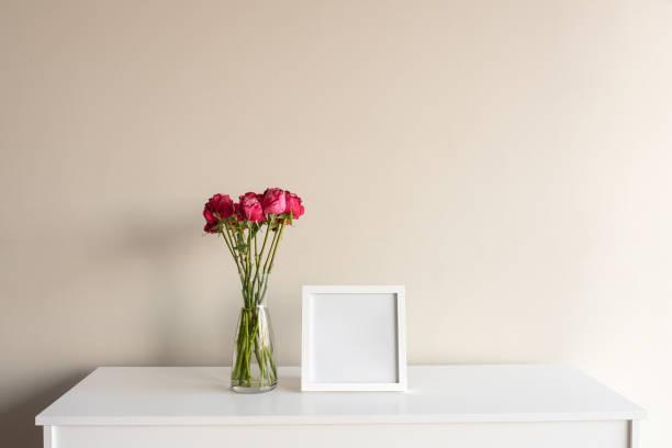 bunte rote rosen mit leeren quadratischen bilderrahmen - anrichte weiß stock-fotos und bilder