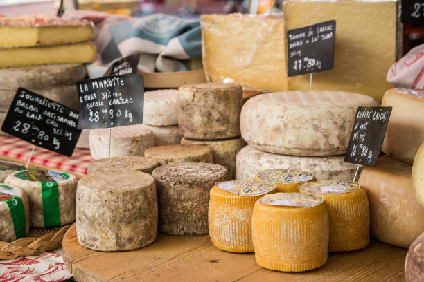 Varieties of french cheeses for sale at a market in Provence Photo captures assortment of cheeses on display at a typical french market. french culture stock pictures, royalty-free photos & images