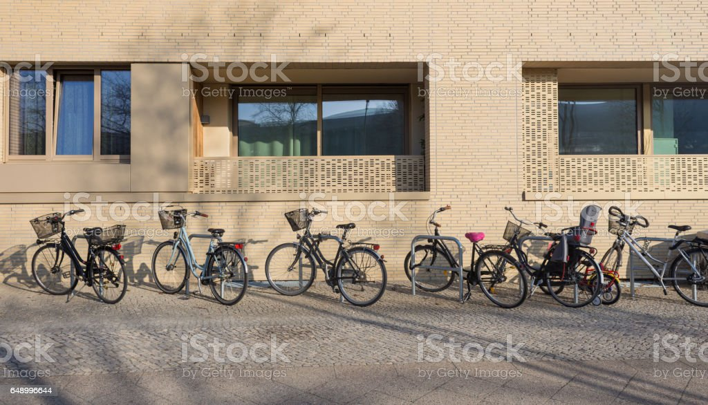 Variety Bicycles parked sidewalk near Apartment Building stock photo