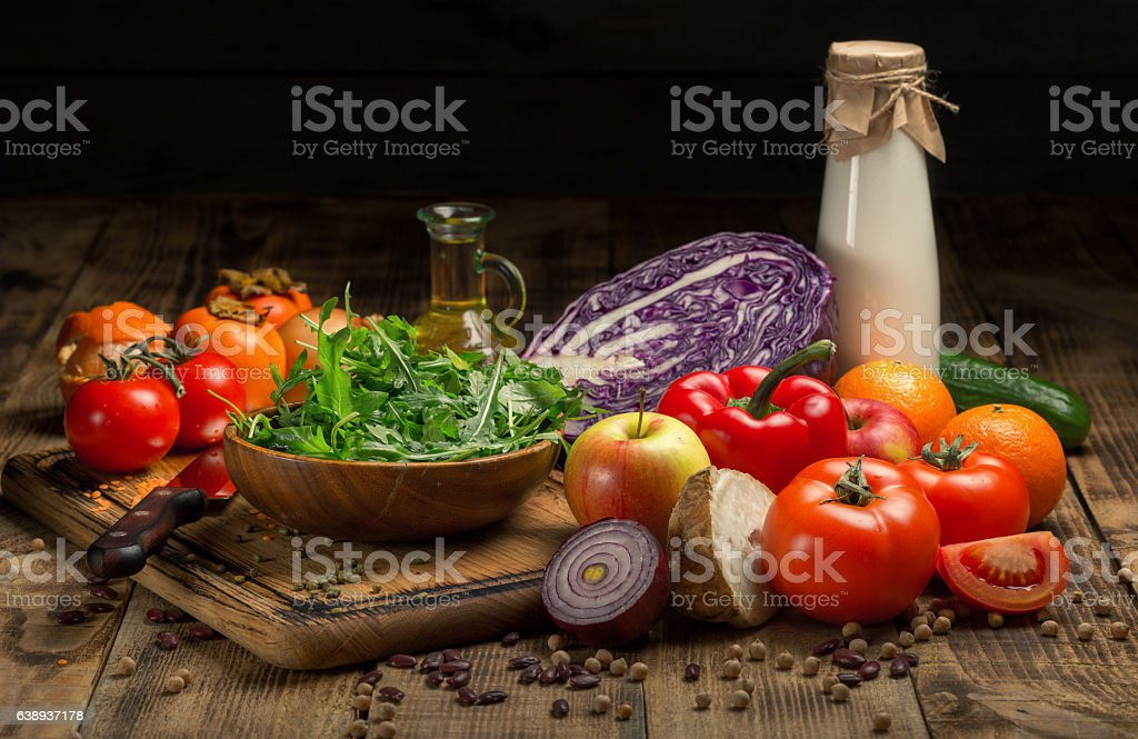 Variety food on a wooden table. Vegetables, fruit, milk and oil on a...