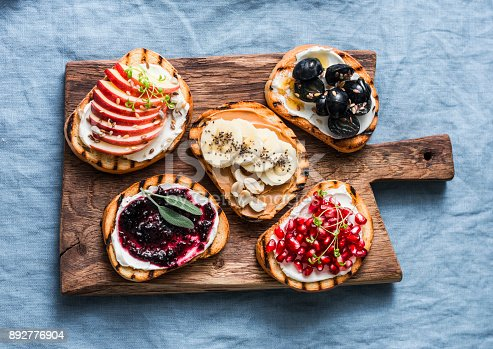 istock Variety grilled bread dessert small plates sandwiches with cream cheese and apple, pomegranate, jam, grapes, peanut butter, banana, flax seed, chia, nuts on a rustic cutting board on blue background, top view. Flat lay. Delicious breakfast or snack 892776904